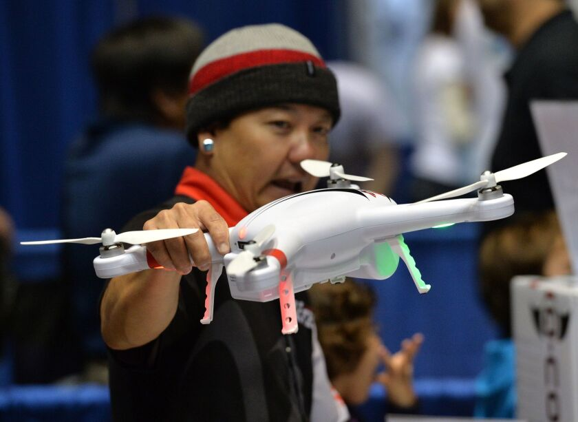 A consultant holds a drone by firm HiTec during the first-ever Drone Expo in Los Angeles last December. Since then, consumer drone sales have soared - and are still climbing.