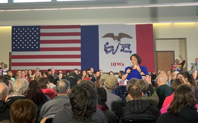 Rep. Katie Porter standing among a crowd with U.S. and Iowa flag designs behind he