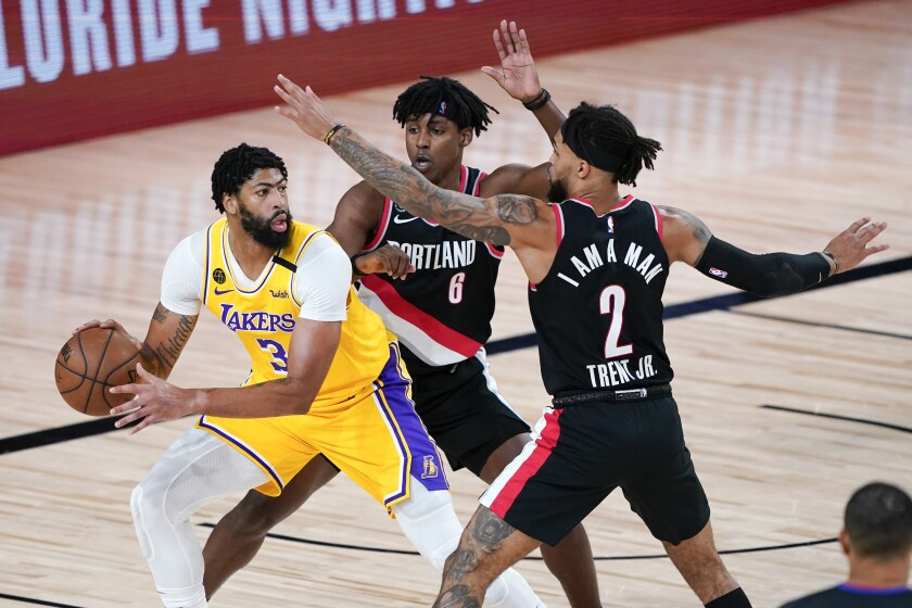 Lakers' Anthony Davis looks for a way past Portland Trail Blazers' Jaylen Hoard and Gary Trent Jr.
