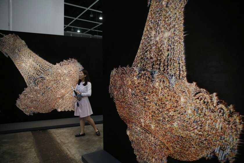 "A woman walks past an artwork ""Chandeliers for Five Cities"" created by South Korean artist Ham Kyungah during the VIP preview of the art fair ""Art Basel"" in Hong Kong, Tuesday, March 22, 2016. Ham presented ""Chandeliers in Five Cities,"" the latest in her series of embroidered works crafted with the help of unidentified North Korean workers. Ham settled on chandeliers as a reference to political power after she noticed one in a picture of world leaders meeting to divide the Korean Peninsula into north and south at the end of World War II. (AP Photo/Kin Cheung)"