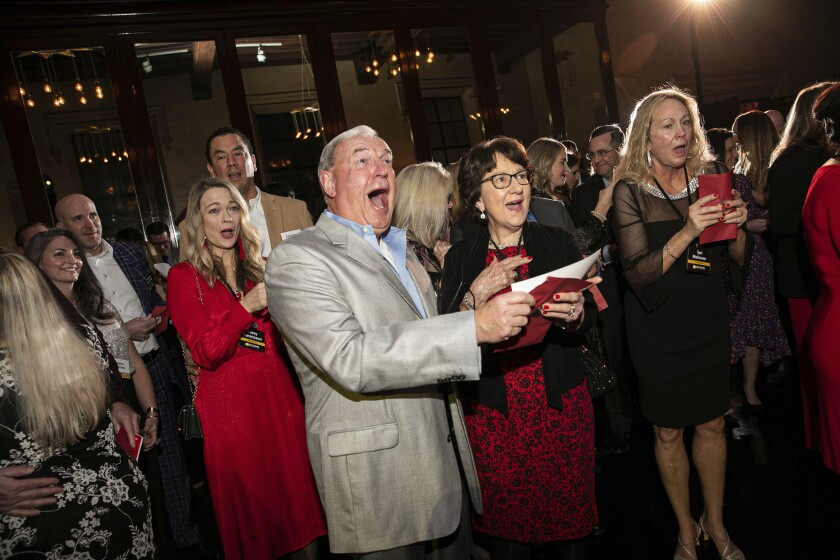 In this image released by St. John Properties, employees of the Maryland real estate firm react after finding out the company is surprising them with $10 million in bonuses at a holiday party, Saturday, Dec. 7, 2019, in Baltimore. (Wendy Hickok Photography via AP)