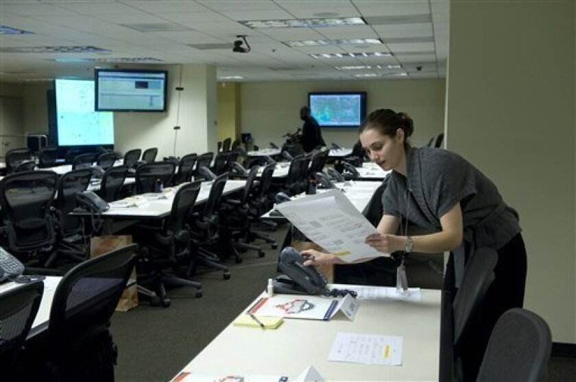 Laura Perret, an intern with the Secret Service, checks to see if the phones are working in the Multi-Agency Communications Center (MACC) for inauguration security operations,  Friday, Jan. 16, 2009,  in Washington.   (AP Photo/Kevin Wolf)