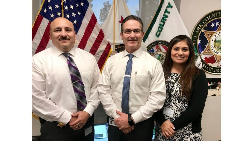Tulare County Sheriff Mike Boudreaux flanked by Capt. Gabriel Macias and Deputy Monserrat Meza.