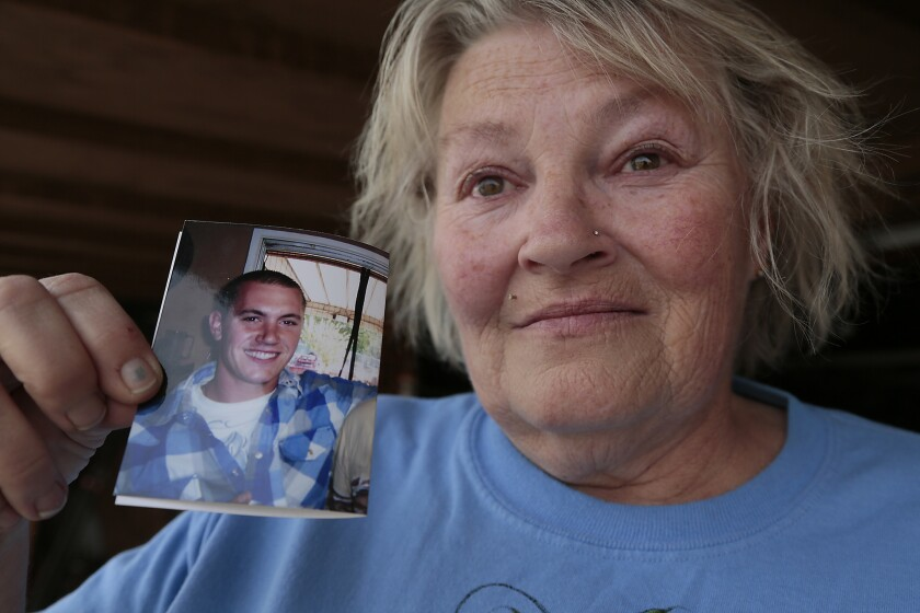 Anne Clemenson holds a photo of her son, Francis Pusok, who was beaten by San Bernardino County sheriff's deputies following a pursuit.