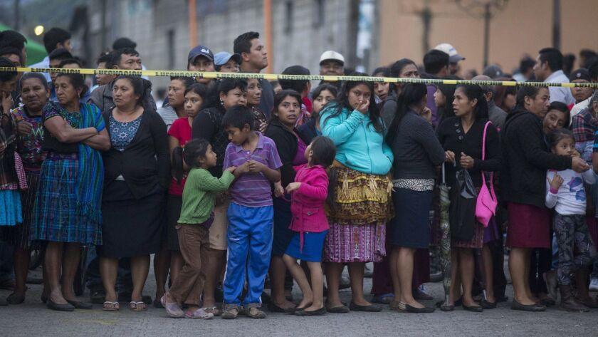 Neighbors stand outside a temporary morgue near Volcan de Fuego or Volcano of Fire in Alotenango, Gu