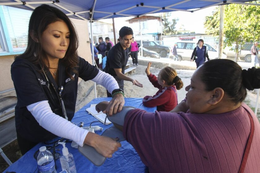 Mitzi Albano checks the blood pressure of Angelica Herrera during the monthly health clinic hosted by the San Diego State University chapter of Flying Samaritans. The clinic is in the Ejido Matamoros area of Tijuana. / photo by Hayne Palmour IV * U-T