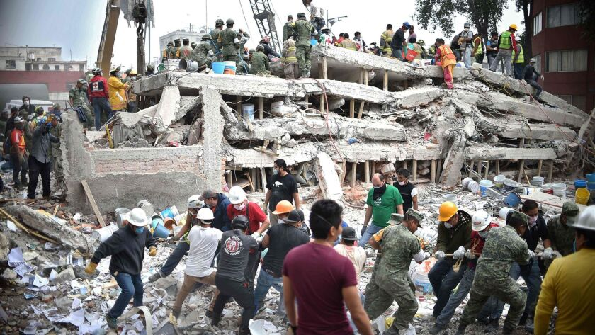 Rescuers, firefighters, police, soldiers and volunteers search for survivors in a flattened building