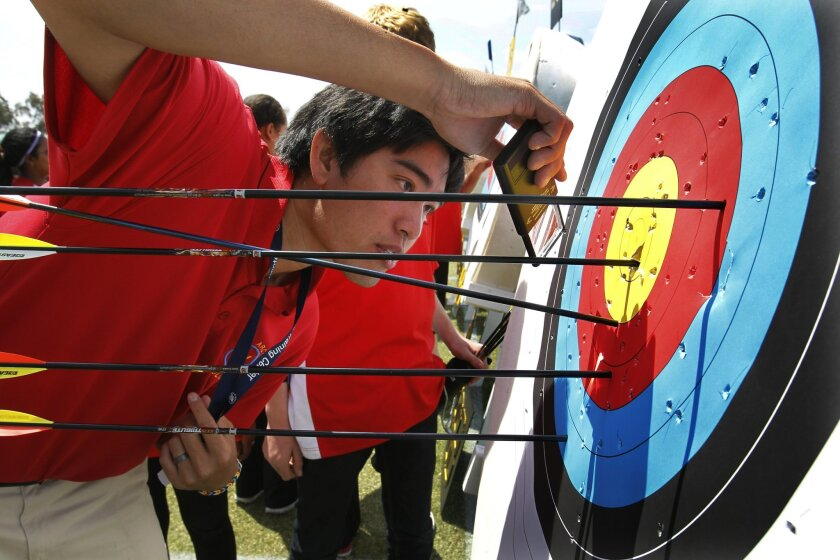 Keaton Chia, the program supervisor for the Easton Sports Development Foundation and the Olympic Archery in Schools program, rules on a shot by using a magnifying glass.