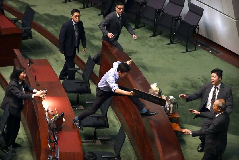 Security officers pursue pro-democracy lawmaker Au Nok-hin, center, as he leaps across desks at the Legislative Council in Hong Kong on Thursday. Nok-hin was chasing leader Carrie Lam as Lam left a question and answer session with lawmakers.