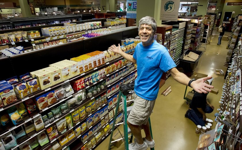 Standing on a ladder above the store aisle, Jimbo Someck, owner of Jimbo's Naturally, takes a brief moment to show off his newest store soon to open this week in Horton Plaza.