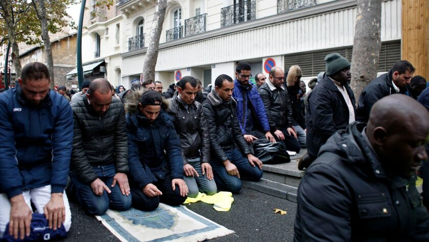 Muslims pray in the street for Friday prayer in the Paris suburb of Clichy la Garenne, Friday, Nov.
