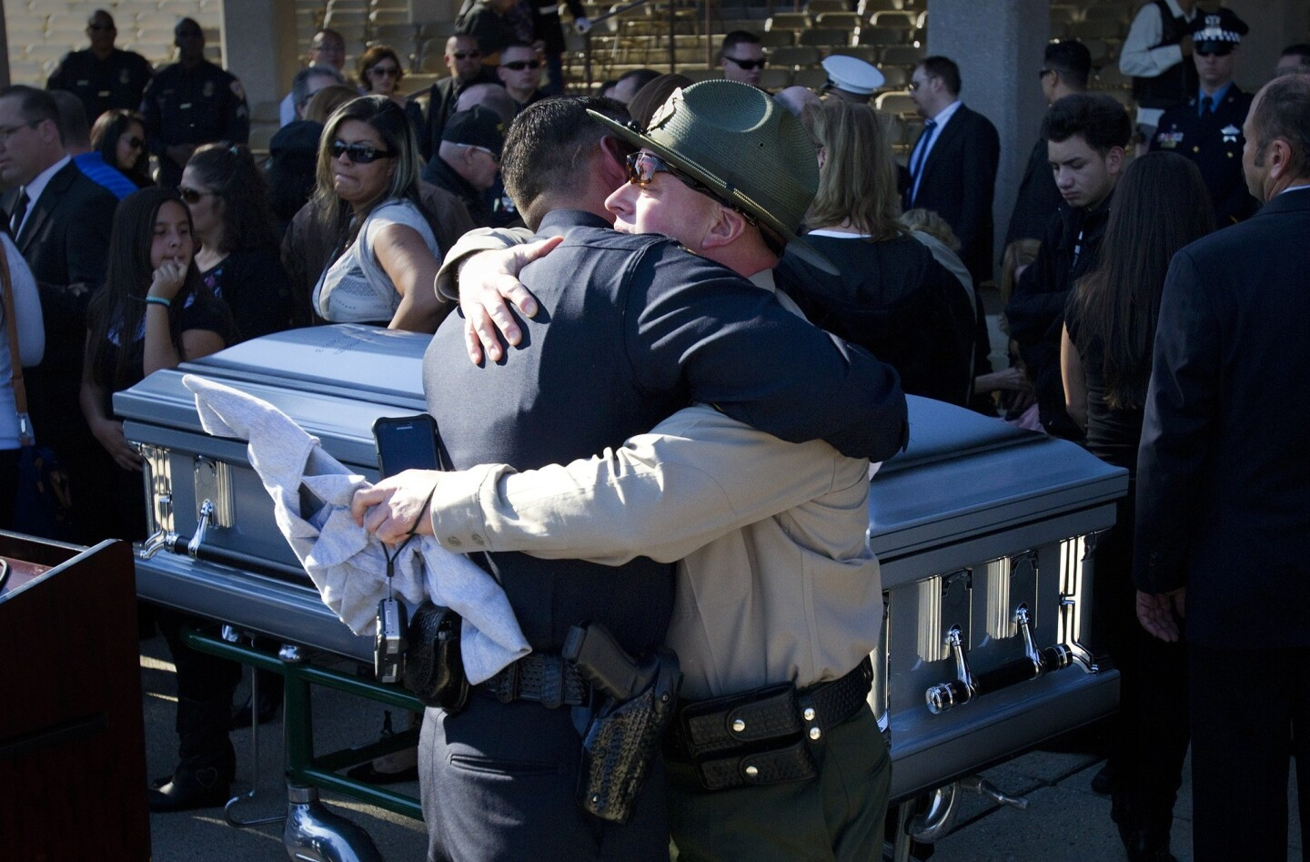 Law enforcement officers embrace at the casket of slain Riverside Police Officer Michael Crain after a memorial service at Riverside National Cemetery.