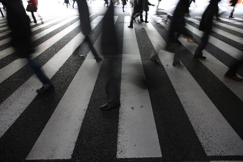 People walk a pedestrian crossing in Tokyo Friday, Feb. 27, 2015. Japanese factories churned out more machinery and electronic devices in January as export shipments rose, but lower energy costs due to cheaper crude oil failed to provide a long-awaited boost to consumer spending. (AP Photo/Eugene Hoshiko)