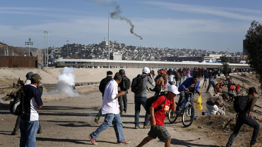U.S. Border Patrol deploy tear gas on migrants refusing to step away from the concertina wire set up along the U.S. Mexico border near San Ysidro on Sunday, Nov. 25.