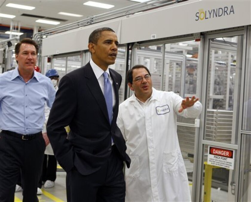 FILE - In this May 26, 2010, file photo, President Obama, center, is given a tour of Solyndra by Executive Vice President Ben Bierman, right, as Chief Executive Officer Chris Gronet, left, walks along at Solyndra Inc. in Fremont, Calif. President Barack Obama said Monday, Oct. 3, 2011, he does not regret a $528 million loan to thecompany that later collapsed, saying officials always knew a clean energy loan program would not back winners 100 percent of the time. (AP Photo/Paul Chinn, Pool, File)