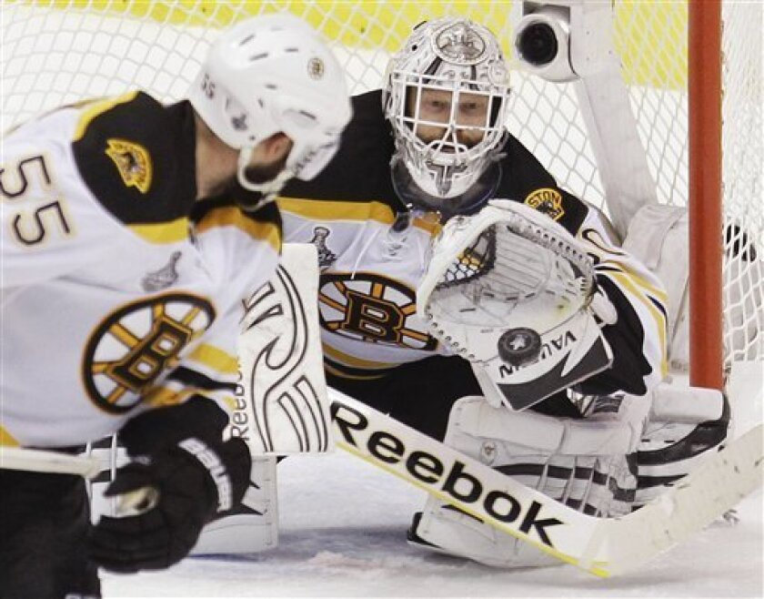 Boston Bruins goalie Tim Thomas (30) makes a save as Boston Bruins defenseman Johnny Boychuk (55) looks on the the second period against the Vancouver Canucks during Game 5 of the NHL hockey Stanley Cup Finals, Friday, June 10, 2011, in Vancouver, B.C. (AP Photo/Julie Jacobson)