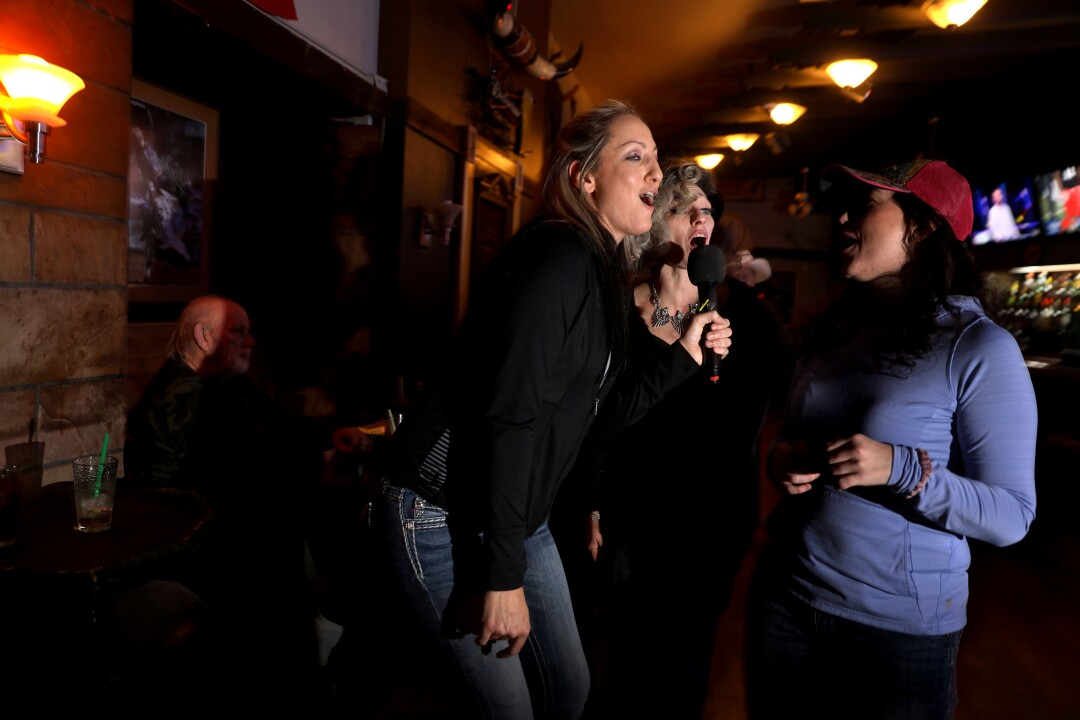 A group of women, none with masks, lean in to sing karaoke around one microphone in a bar