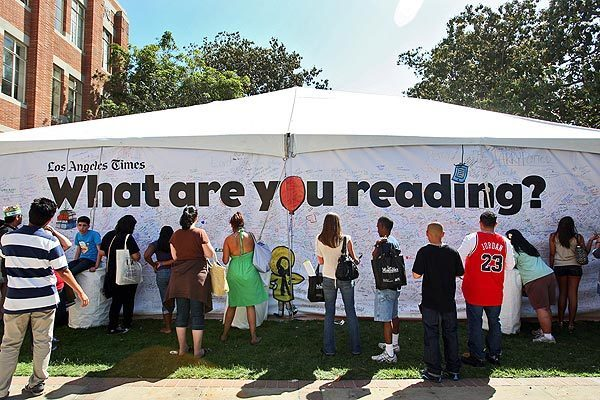 On one of the hundreds of tents set up across the USC campus, Los Angeles Times Festival of Books attendees write the titles of the books they're reading — or are about to read. See full story