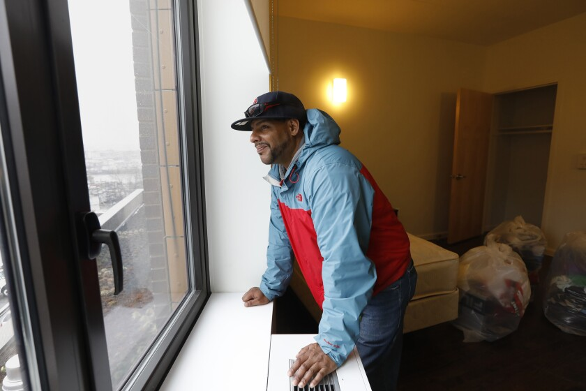 BRONX, NEW YORK--APRIL 14, 2018--Jesus Melendez, age 46, looks at the view out his new studio apartm