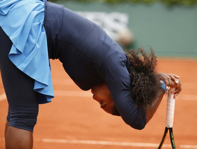 Serena Williams of the U.S. leans on her racket after missing a return in the semifinal match of the French Open tennis tournament against Netherlands' Kiki Bertens at the Roland Garros stadium in Paris, France, Friday, June 3, 2016. (AP Photo/Alastair Grant)