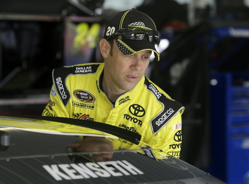NASCAR Sprint Cup Series driver Matt Kenseth climbs into his race car in garage area at Pocono Raceway during practice for Sunday's NASCAR Sprint Cup Series auto race in Long Pond, Pa., Friday, June 6, 2014. (AP Photo/Mel Evans)