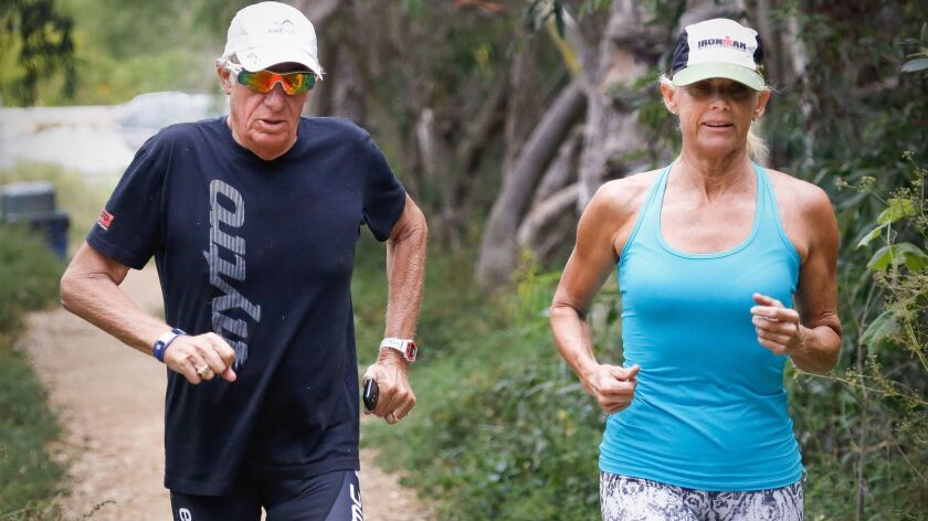 Mike Levine, 68, of Carlsbad and Kathleen McCartney, 58, of La Jolla go for a training run to prepare for the 2017 Ironman World Championship in Kona, Hawaii, on Oct. 18. Levine has stage 4 pancreatic cancer.