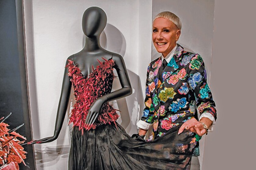 """Jan Arnold with a Ruby Corset made of hundreds of nail tips by designers David and Phillipe Blond. She is the co-producer of """"Tiny Canvases: The Art of Nails"""" exhibit, on display through Feb. 9, 2020 at Oceanside Museum of Art."""