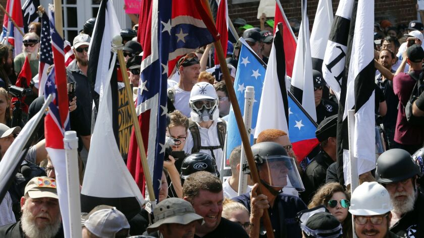 Surrounded by counterprotesters, white nationalist demonstrators walk into Lee Park in Charlottesville, Va., on Aug. 12, 2017.