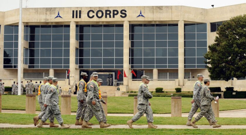 Soldiers walk past the III Corps building headquarters at Ft. Hood near Killeen, Texas.