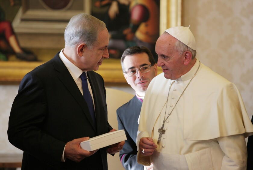 Pope Francis exchanges gifts with Israeli Prime Minister Benjamin Netanyahu during a private audience at his library in Vatican City.
