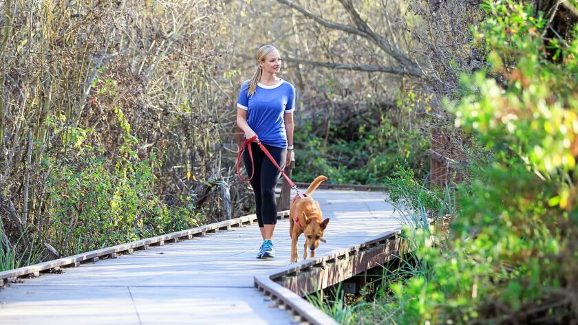 Food and fitness blogger Nicole Crane walks with her dog Harley along the Lake Calavera trail in Carlsbad.