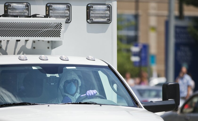 An ambulance transporting Nancy Writebol, an American missionary stricken with Ebola, arrives at Emory University Hospital, Tuesday, Aug. 5, 2014, in Atlanta. Writebol is expected to be admitted to Emory University Hospital on Tuesday, where she will join another U.S. aid worker, Dr. Kent Brantly,