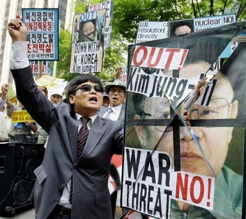 """Pro-U.S. and anti-North Korea protesters shout slogans as they hold pictures of North Korean leader Kim Jong Il during an anti-North Korea and """"welcome ceremony"""" of a special envoy for President Barack Obama, Stephen Bosworth in front of Foreign Ministry in Seoul, South Korea, Friday, May 8, 2009. North Korea vowed Friday to bolster its atomic arsenal in response to what it called Washington's """"persistent hostile policy,"""" even as a special envoy for President Barack Obama traveled to the region in a bid to draw Pyongyang back to nuclear negotiations. (AP Photo/Lee Jin-man)"""