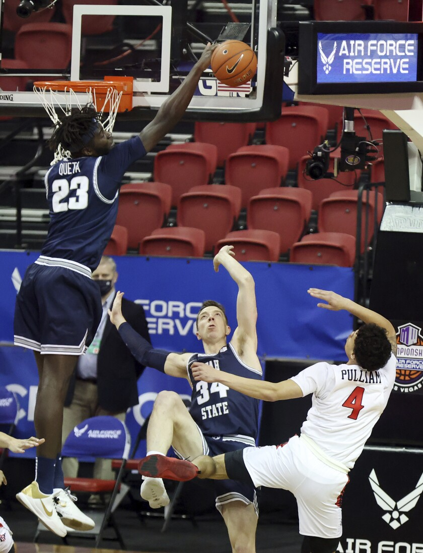 Utah State center Neemias Queta (23) blocks a shot from San Diego State guard Trey Pulliam (4) as Utah State forward Justin Bean (34) defends during the first half of an NCAA college basketball game in the championship round of the Mountain West Conference tournament, Saturday, March 13, 2021, in Las Vegas. (AP Photo/Isaac Brekken)