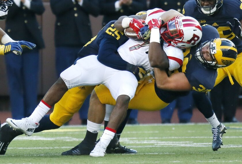 Rutgers' Robert Martin (7) is tackled by Michigan's Dymonte Thomas (25) and Joe Bolden (35) during the first half of an NCAA college football game Saturday, Nov. 7, 2015, in Ann Arbor, Mich. (AP Photo/Duane Burleson)