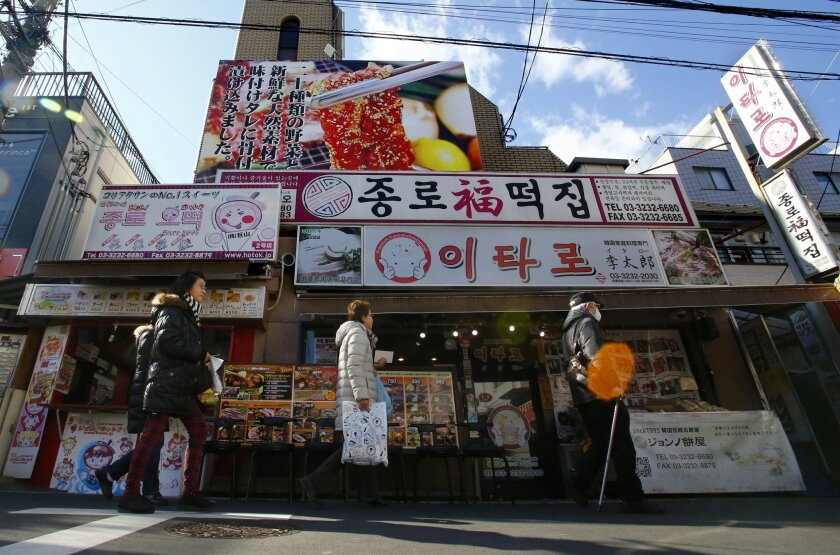 In this Wednesday, Feb. 10, 2016 photo, people walk by a Korean restaurant in Tokyo's Korean district. Japan has a half-million ethnic Korean residents, and the pro-North Korean community is estimated to make up 30,000 to 100,000 of them. Most of them are descendants of Koreans who came to Japan du