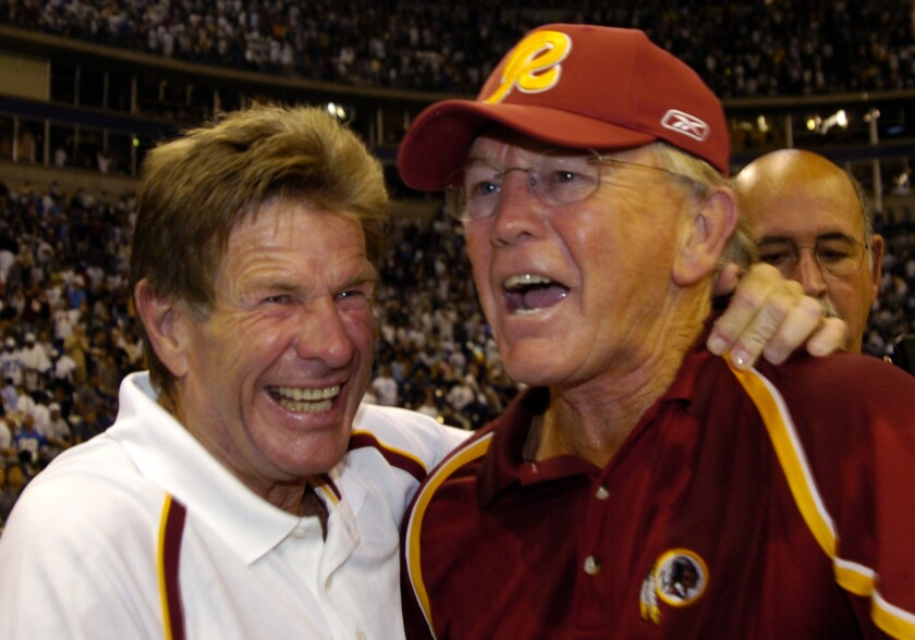 Redskins offensive line coach Joe Bugel (left) and head coach Joe Gibbs celebrate a win over Dallas in 2005.