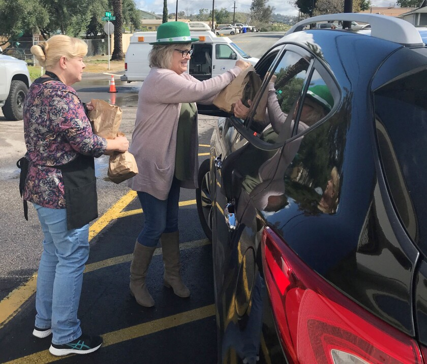 Ramona Unified School District staff distribute free sack meals at curbside during school closure.