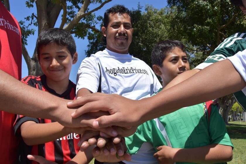 Fotografía fechada el 1 de junio de 2018 que muestra al inmigrante mexicano Eduardo Chamú (c) mientras cruza su manos con sus hijos Jefferson (12) (i) y Jason (12) (d), en el parque TeWinkle en Costa Mesa, California (EE.UU.). EFE