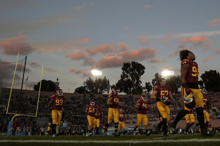 USC defensive players jog off the field after warming up before a game against UCLA at the Rose Bowl.