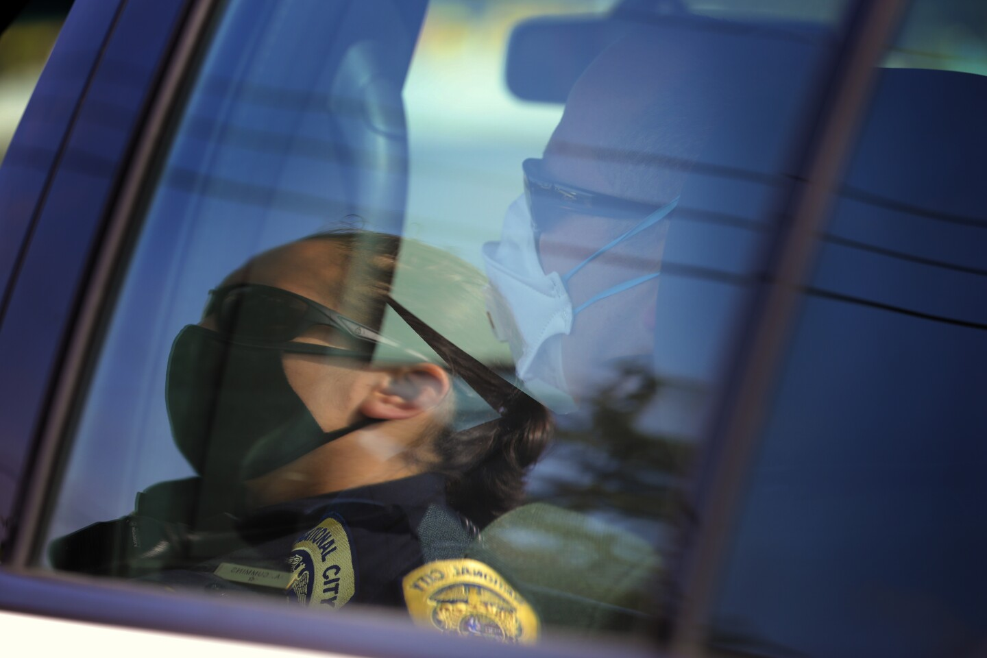 Soon after their routine squad line at police headquarters, National City Police Officer Ashley Cummins meets in the field with Sgt. Aaron DePascale. To protect officers from the possibility of being exposed to the coronavirus, officers at National City police Department where protective mask and eye protection.