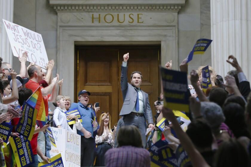 El representante demócrata Warwick Sabin (centro) se suma a manifestantes frente a la cámara baja de la Legislatura de Arkansas contra la aprobación de un proyecto de ley de objeción religiosa que según los detractores permitiría la discriminación de gays y lesbianas.