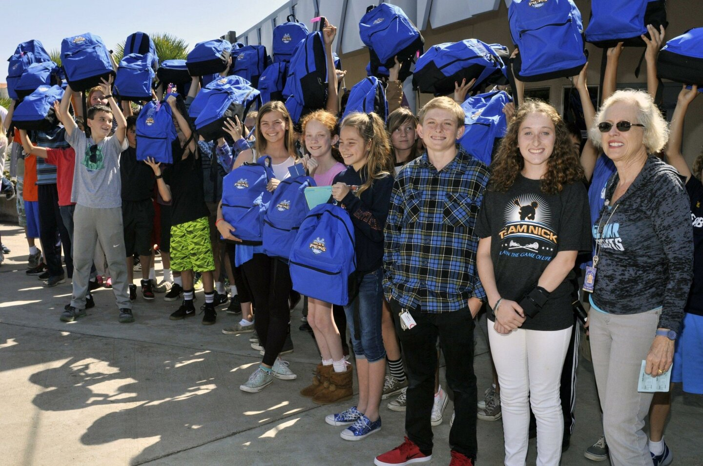 Nick's Picks founder Nick Wallace, Lexie Wallace, Del Mar Heights Principal Wendy Wardlow and students with forty seven full backpacks