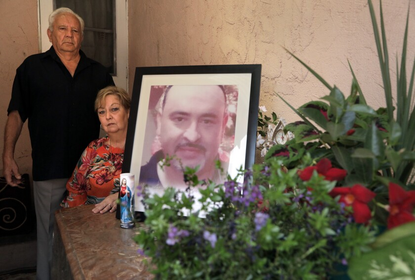 Juan and Blanca Briceno pose next to a large framed photo of their late son next to a candle