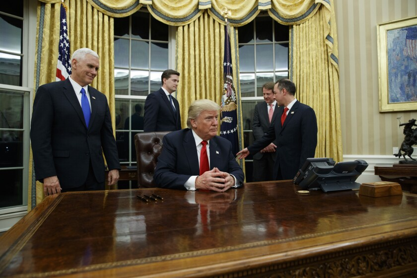 President Donald Trump prepares to sign his first executive order in the newly refurbished Oval Office, where the curtains have been switched from red to gold.