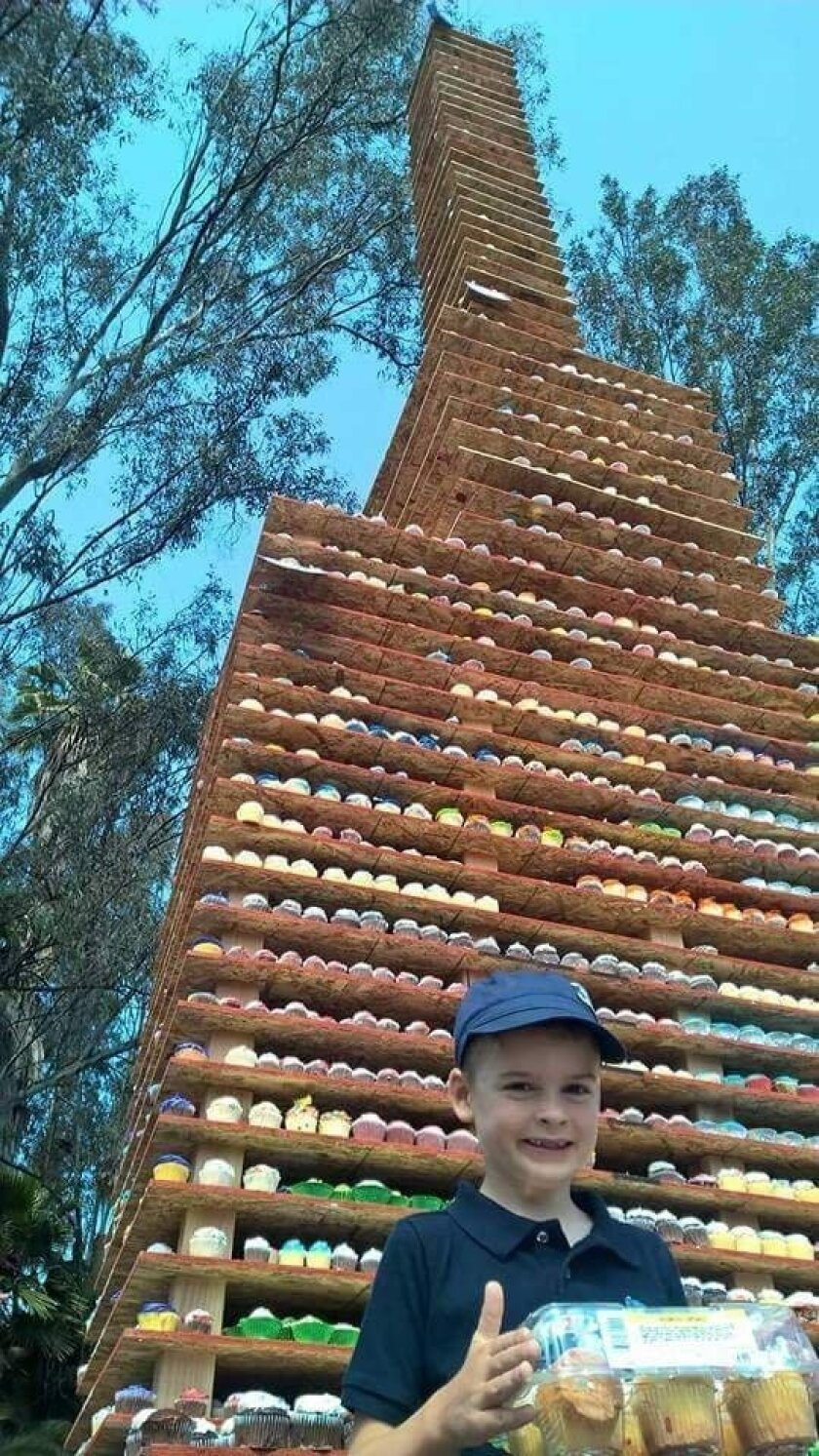 A satisfied customer at what appears to be the world's largest cupcake tower at 31.5 feet with 25,103 cupcakes.