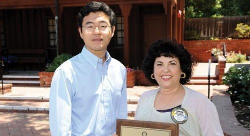 Marlene Gotz, past president of the Rotary Club of Del Mar, presents the Erik Scott Sorensen Service Above Self award to Michael P. Kim.