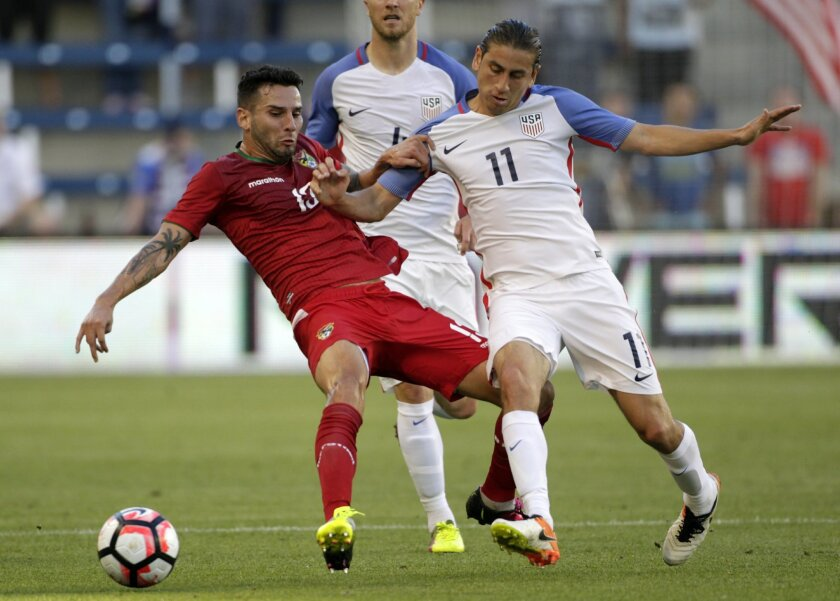 Bolivia midfielder Alejandro Melean (13) and U.S. midfielder Alejandro Bedoya (11) battle for control of the ball in the first half of a men's international friendly soccer match, Saturday, May. 28, 2016, in Kansas City, Kan. (AP Photo/Colin E. Braley)