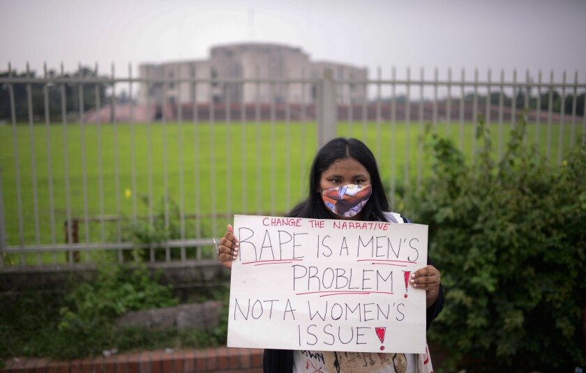 A women's rights activist among those protesting against gender based violence holds a placard outside the Parliament in Dhaka, Bangladesh, Friday, Oct.9, 2020. Bangladesh's Cabinet has approved an increase in the maximum punishment in rape cases to death from life imprisonment after a series of recent sexual assaults triggered protests. (AP Photo/ Mahmud Hossain Opu)