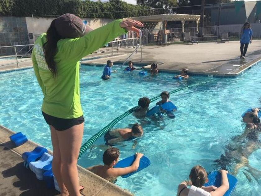 A YMCA swim instructor shows students the right form for paddle-board swimming.